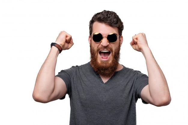 Giovane uomo barbuto che fa il gesto del vincitore con la sua mano che grida ad alta voce.