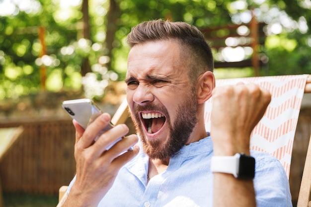 Giovane uomo barbuto all'aperto utilizzando il telefono cellulare
