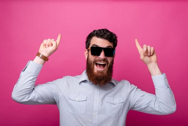 Giovane uomo barbuto che punta con entrambe le mani verso l'alto con un viso eccitato indossando occhiali da sole su sfondo rosa.