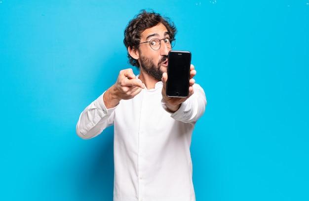 Giovane uomo barbuto che mostra il suo schermo cellulare