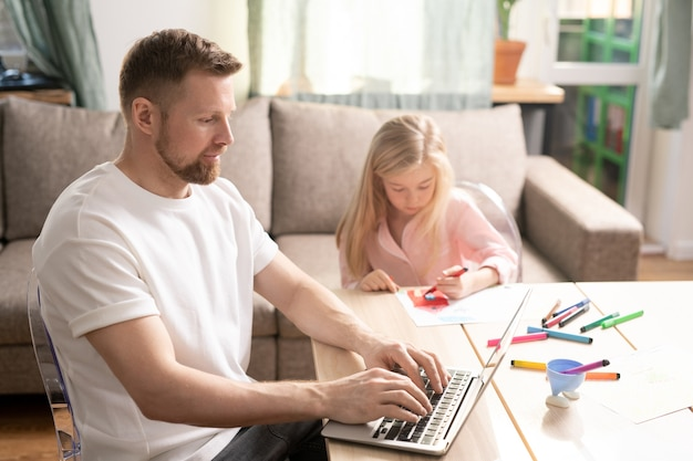 Giovane uomo barbuto seduto a tavola davanti al laptop e lavora in remoto mentre la sua piccola figlia disegna con evidenziatori nelle vicinanze