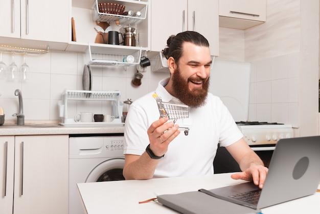 Giovane uomo barbuto seduto in cucina davanti al computer portatile e comprare qualcosa online