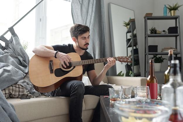 Giovane uomo barbuto seduto sul divano con tende e suonare la chitarra in appartamento dopo la festa
