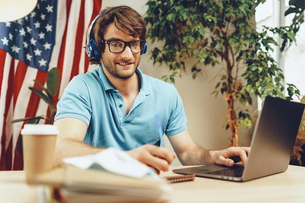 Giovane uomo barbuto seduto a tavola con laptop e bandiera americana