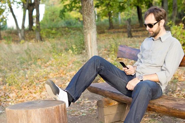 Giovane uomo barbuto seduto su una panca in legno in campagna mandare sms sul suo cellulare o telefono cellulare