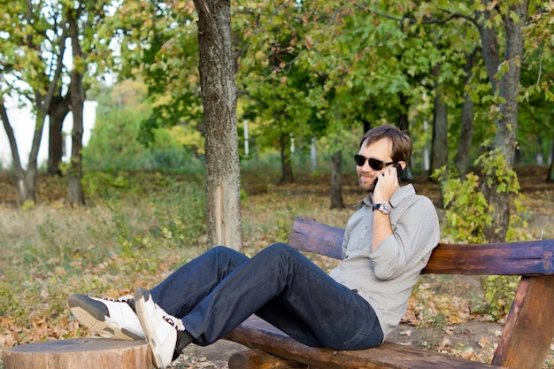 Giovane uomo barbuto seduto su una panchina in legno del paese sotto il sole in chat sul suo telefono cellulare