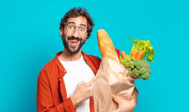 Giovane uomo barbuto che sorride allegramente, sentendosi felice e indicando di lato e verso l'alto, mostrando l'oggetto nello spazio della copia e tenendo in mano un sacchetto di verdure
