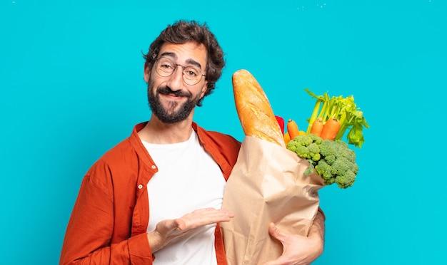 Giovane uomo barbuto che sorride allegramente, si sente felice e mostra un concetto nello spazio della copia con il palmo della mano e tiene in mano un sacchetto di verdure