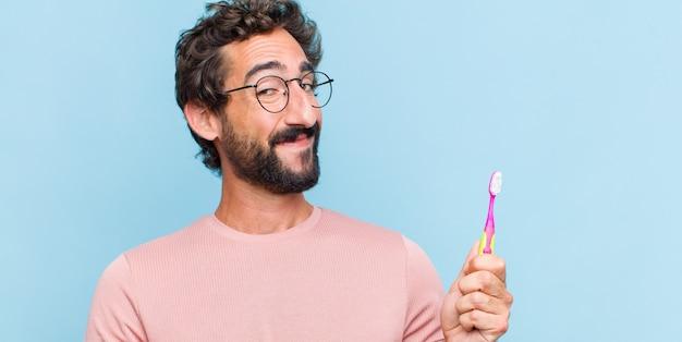 Giovane uomo barbuto sorridente, fiducioso, di successo e felice, mostrando il concetto o l'idea sullo spazio della copia sul lato