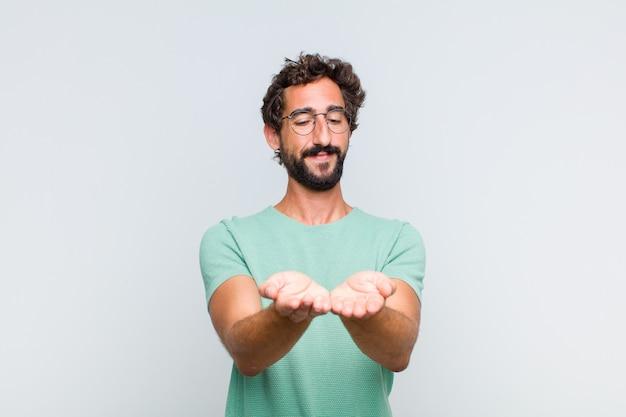 Giovane uomo barbuto che sorride felicemente con uno sguardo amichevole, fiducioso, positivo, offrendo e mostrando