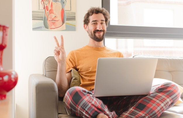 Giovane uomo barbuto sorridente e guardando amichevole che mostra il numero due o secondi con la mano in avanti il conto alla rovescia e seduto con un computer portatile