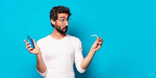 Giovane uomo barbuto che fuma con un vaper