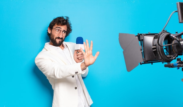 Presentatore televisivo di giovane uomo barbuto.
