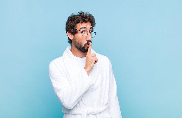 Giovane uomo barbuto che indossa un accappatoio chiedendo silenzio e tranquillità