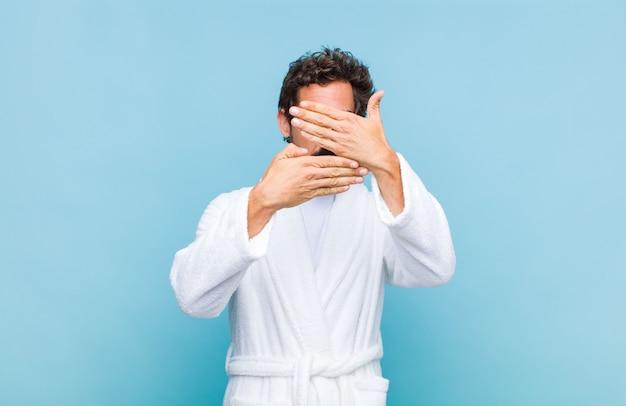 Giovane uomo barbuto che indossa un accappatoio che copre il viso con entrambe le mani