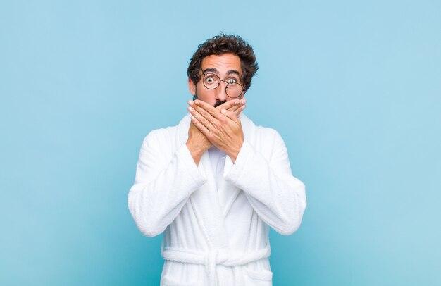 Giovane uomo barbuto che indossa un accappatoio che copre la bocca con le mani con un'espressione scioccata e sorpresa