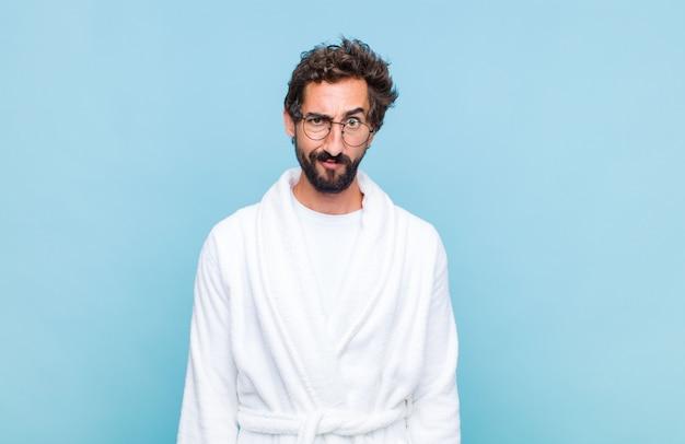 Giovane uomo barbuto che indossa un accappatoio sentendosi confuso e dubbioso, chiedendosi o cercando di scegliere o prendere una decisione