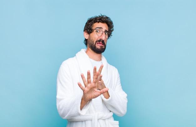 Giovane uomo barbuto che indossa un accappatoio sensazione di disgusto e nausea