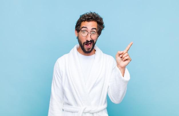 Giovane uomo barbuto che indossa un accappatoio sentirsi felice