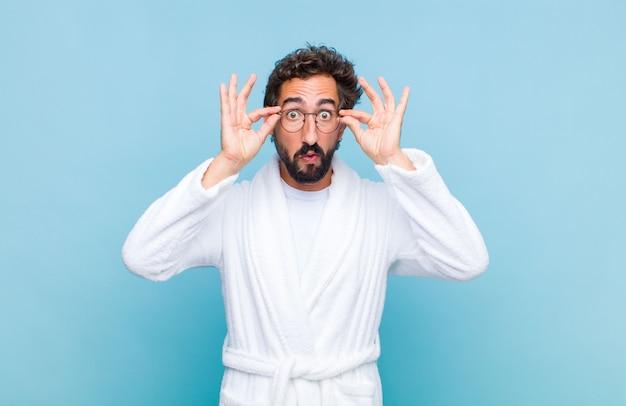 Giovane uomo barbuto che indossa un accappatoio sentirsi scioccato, stupito e sorpreso, tenendo gli occhiali con uno sguardo stupito e incredulo