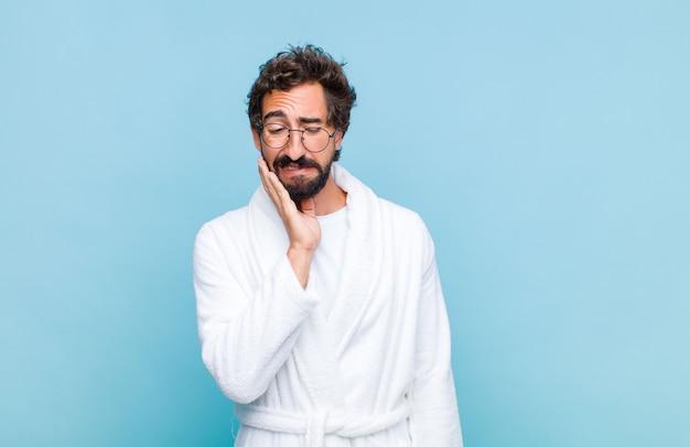 Giovane uomo barbuto che indossa un accappatoio tenendo la guancia e soffre di doloroso mal di denti, sensazione di malessere, miserabile e infelice, alla ricerca di un dentista