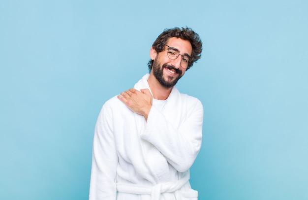 Giovane uomo barbuto che indossa un accappatoio che ride allegramente e con sicurezza