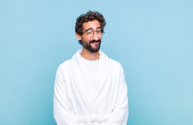 Giovane uomo barbuto che indossa un accappatoio che sembra felice e amichevole, sorridente e ammiccante con un atteggiamento positivo