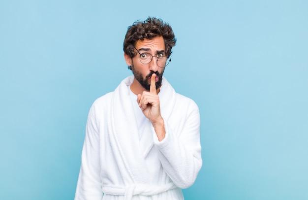 Giovane uomo barbuto che indossa un accappatoio alla ricerca seria