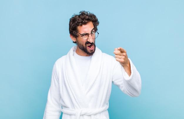 Giovane uomo barbuto che indossa un accappatoio che punta alla telecamera con un'espressione aggressiva arrabbiata