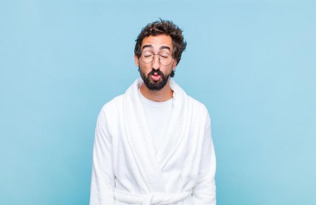 Giovane uomo barbuto che indossa un accappatoio premendo le labbra insieme a un'espressione adorabile