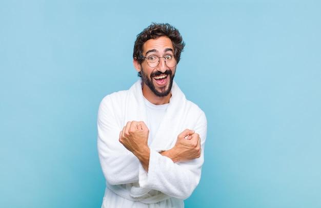 Giovane uomo barbuto che indossa un accappatoio sorridendo allegramente e celebrando