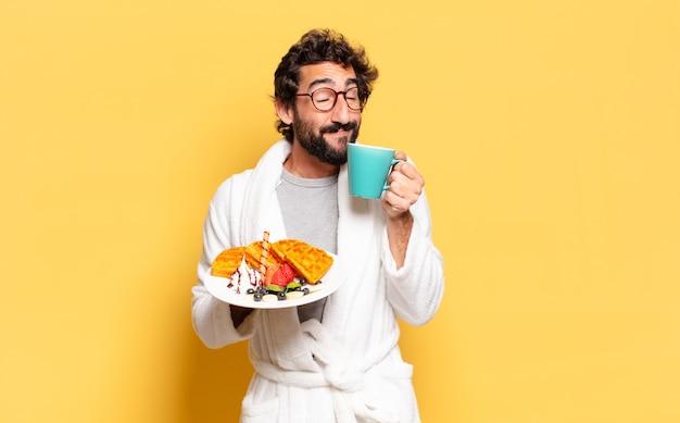 Giovane uomo barbuto che indossa accappatoio e fare colazione