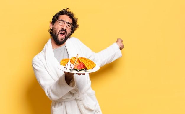 Giovane uomo barbuto che indossa accappatoio e fa colazione