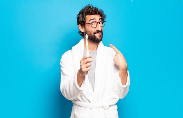 Giovane uomo barbuto che indossa accappatoio e spazzolino da denti