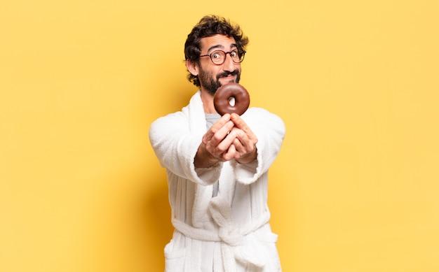Giovane uomo barbuto che indossa accappatoio con una ciambella al cioccolato