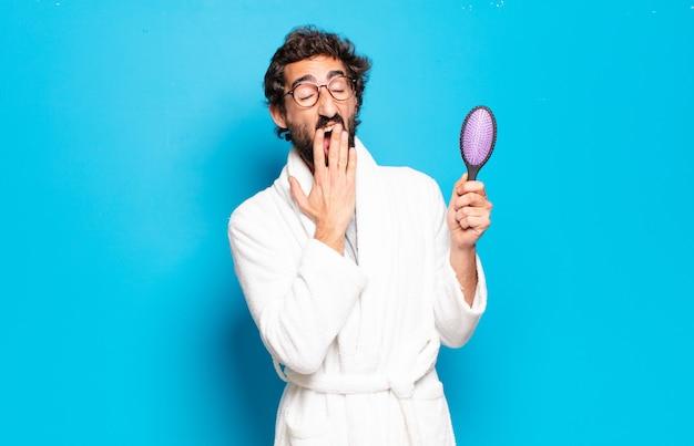 Giovane uomo barbuto che indossa accappatoio con una spazzola per capelli