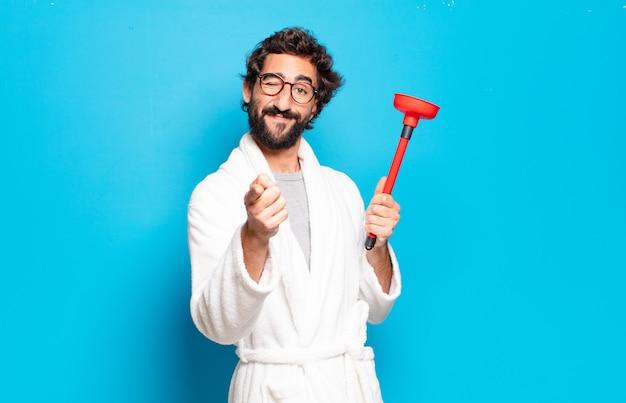 Giovane uomo barbuto che indossa accappatoio con uno stantuffo