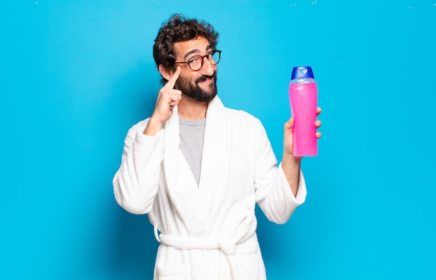 Giovane uomo barbuto che indossa accappatoio con shampoo e prodotti di bellezza