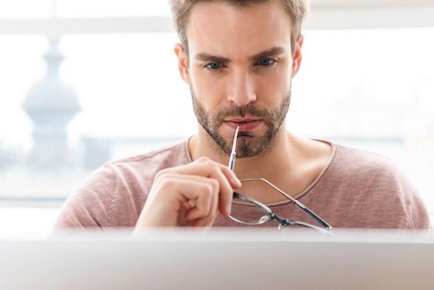 Giovane uomo barbuto che indossa occhiali da vista che lavora al computer portatile dalla finestra nella caffetteria al chiuso