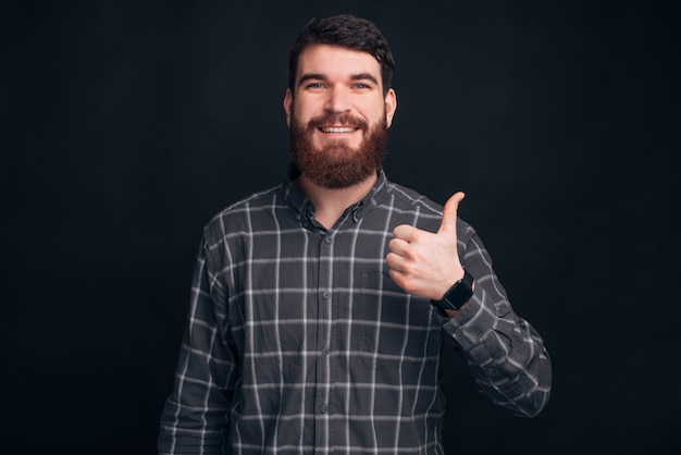 Il giovane uomo barbuto che indossa una camicia, sta mostrando come o pollice sul gesto sul muro nero