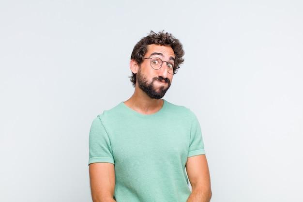 Giovane uomo barbuto con un'espressione sciocca, pazza, sorpresa, guance gonfie, sentirsi imbottito, grasso e pieno di cibo