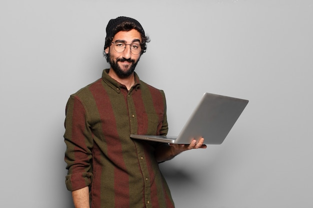 Giovane uomo barbuto con un computer portatile