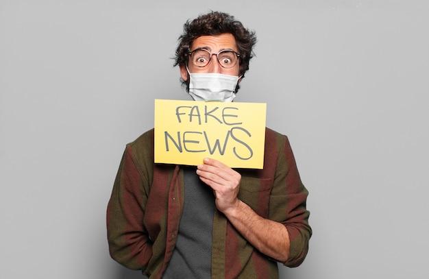 Giovane uomo barbuto con una maschera medica e un concetto di notizie false