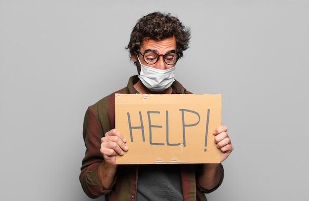 Il giovane uomo barbuto con una maschera medica aiuta il concetto