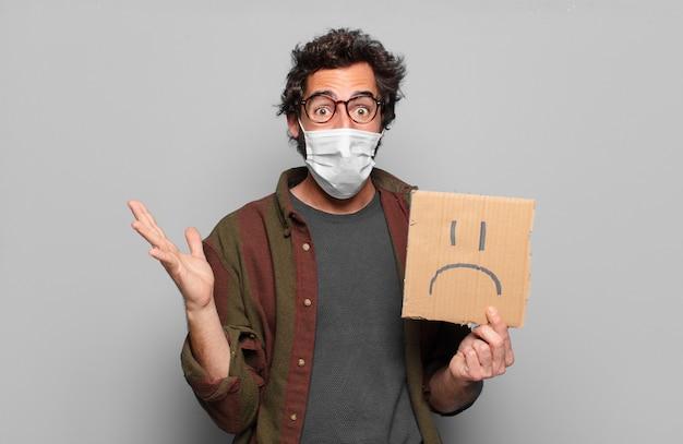 Giovane uomo barbuto con una maschera medica e un concetto di banner triste