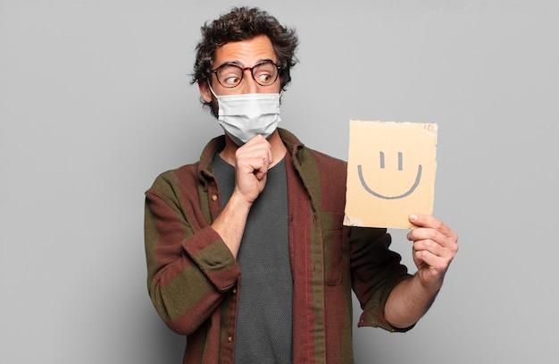 Giovane uomo barbuto con una mascherina medica con un concetto di sile