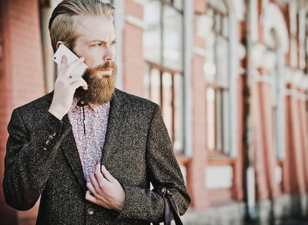 Giovane uomo barbuto con cellulare, all'aperto, ora legale