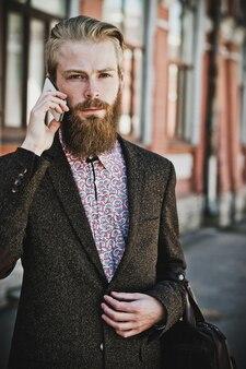 Giovane uomo barbuto con mobile, all'aperto, estate