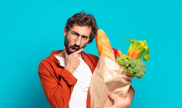 Giovane uomo barbuto con la bocca e gli occhi spalancati e la mano sul mento, sentendosi spiacevolmente scioccato, dicendo cosa o wow e tenendo in mano un sacchetto di verdure