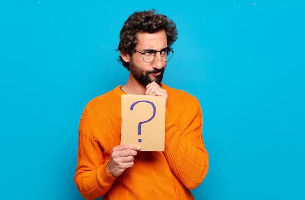 Giovane uomo barbuto con un punto interrogativo